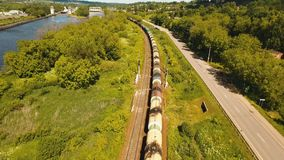 Freight train on the railway. Freight train with cisterns and containers on the railway. Aerial view Container Freight Train, Locomotive in the countryside stock footage