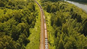 Freight train on the railway. Freight train with cisterns and containers on the railway. Aerial view Container Freight Train, Locomotive in the countryside. 4K stock video footage