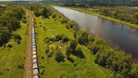 Freight train on the railway. Freight train with cisterns and containers on the railway. Railway and highway with cars. Aerial view Container Freight Train stock footage