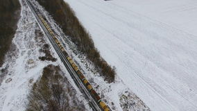 Freight train on the railway in winter. Gasoline, fuel tanks. Aerial shot. stock video footage