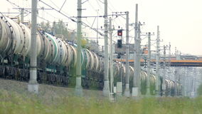Freight train rides by rail away into the distance. It consists of wagons with tanks painted in beige and brown colors. Saint-Petersburg, Russia, 2016 stock footage