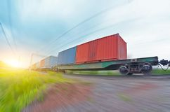 Freight train rides at speed with container and cargo at sunset. Freight train rides at speed with container and cargo at sunset Royalty Free Stock Image