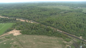 Freight Train rides through the woods, fields and village stock video footage