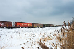 Freight train rolling through snowy field. stock images