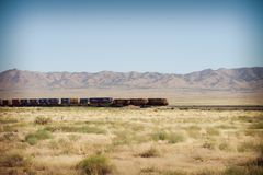 A freight train rolls on the tracks through Death Valley. A freight train rolls through the desert landscape of Death Valley in Arizona stock photos