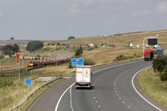 Freight train on Shap and lorries on M6 motorway. A goods train from Carlisle N. Y. to Warrington Bank Quay heads down Shap towards Tebay on the West Coast Main Stock Photo