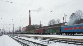 Freight train slow moving on rail station on the background of winter gray sky. And smoke from chimney stock video footage