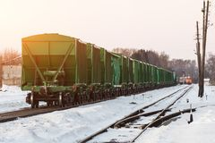 A freight train with a small train of hopper cars, at a small station in winter. A different locomotive is traveling in the distan. Ce Royalty Free Stock Photography