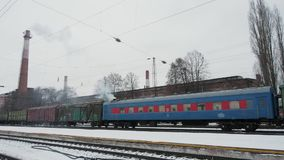 Freight train staying on rail station platform on the background of gray sky. And smoke from chimney stock video