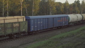 Freight train at sunset. View from the window of the suburban train, sunset stock footage