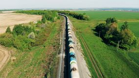 Freight train with tank wagons goes on a long railway near fields. 4K. Freight train with tank wagons goes on a long railway near fields stock video footage