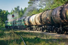 Freight train with tank wagons. Moving in forest royalty free stock image
