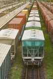 Freight train with tank wagons moving in forest. Green diesel cargo locomotive. Vertical Royalty Free Stock Photography