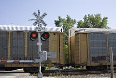 Freight Train on Tracks. Train crossing - gates are down and lights are flashing - clear summer day stock images