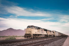 Freight train traveling Arizona desert. Royalty Free Stock Photo