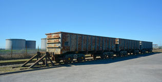 Freight train wagon's. 3 freight train wagons waiting in a siding close to some silo's Stock Photo