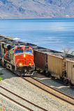 Freight Trains. A powerful diesel locomotive and some railcars on the shore of a lake in British Columbia, Canada Stock Photography