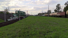 Freight trains and suburban electric train follow in the same direction. Lyubertsy, Moscow region, Russia. 6 Sep 2014. Passenger train of RZD (Russian railway) stock footage