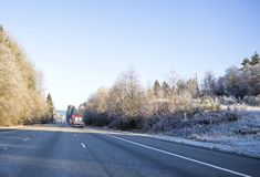 Big rigs semi trucks convoy with commercial cargo on flat bed semi trailers running on wide highway with winter frosty grass and. Freight transport by semi royalty free stock photos