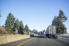 Convoy of big rigs semi trucks of different make and different trailers running on the winter road with frost grass and trees. Freight transport by semi trucks royalty free stock photography