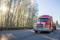 Big rig modern red semi truck with flat bed semi trailer transporting commercial cargo on the road with sun shining through the. Freight transport by semi trucks royalty free stock images