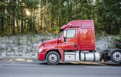 Red big rig semi truck tractor going on the road with green forest on background. Freight transport by semi trucks in America - the main type of logistics. Red stock photo
