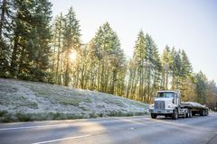 White big rig day cab semi truck for local haul transporting cargo on flat bed semi trailer running on winter road with frost. Freight transport by semi trucks royalty free stock image
