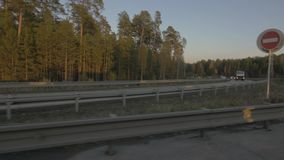 Freight truck and car driving on suburban road on background autumn landscape. Truck and cars moving on suburban road on background autumn forest stock footage
