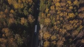 Freight trucks and cars moving on suburban road through autumn forest. Top view from flying drone freight trucks and cars driving on highway road on background stock video