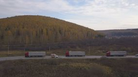 Freight trucks and cars moving on suburban road on background autumn forest. Drone view freight trucks and cars moving on suburban road on background autumn stock video