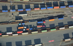 Freight Trucks and Trains. Overhead shot of different colored trucks and shipping containers Stock Photo