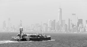 Freight tug pushing cargo ship to the port in New York City and Lower Manhattan skyscarpers skyline in background. stock photo