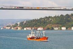 Freighter cruising under the bridge Stock Photos