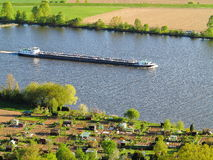 Freighter on Danube river passing allotments Stock Photography