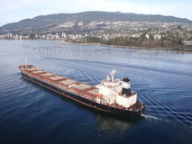 Freighter departs Port of Vancouver. A large freighter sails out of Vancouver harbour, with the north shore mountains serving as an impressive background stock photography