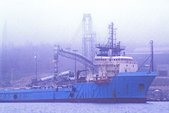 Freighter in the Fog, Nova Scotia, CA. Huge commercial freighter shrouded in fog, anchored in the East River in Nova Scotia, Canada Stock Image