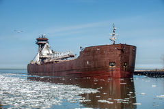 Freighter and Ice. A Great Lakes articulated tugboat and barge moves past a patch of broken ice as it enters the Cuyahoga River in Cleveland, Ohio from Lake Erie royalty free stock image