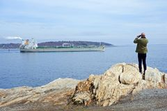 Freighter leaving harbor. Freighter leaving Portland, Maine, harbor, observed from shore by a man with binoculars royalty free stock photo