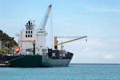 Freighter about to depart. Cargo ship making ready to leave a Caribbean island port (Sint Maarten Royalty Free Stock Image