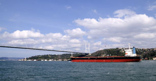 freighter Under Bosphorus Bridge in istanbul Royalty Free Stock Images
