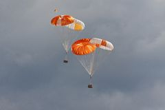 Freights on parachutes go down the earth. Freights on color parachutes go down the earth against cloudy sky Stock Images