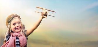 Freiheit zum Traum - frohes Kind, das mit Flugzeug spielt