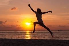 Freiheitskonzept mit dem jungen Jugendlichen glücklich und Sprung auf Strand Stockbild