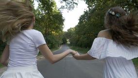 Freiheitskonzept mit den Freundinnen, die auf einer Waldlandstraße laufen - stock video
