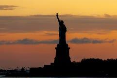 Freiheitsstatue Schattenbild gegen hochroten Sonnenuntergang Lizenzfreies Stockfoto