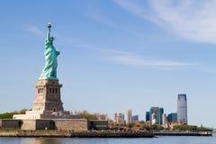 Freiheitsstatue und Manhattan-Skyline hinter ihm Lizenzfreies Stockfoto
