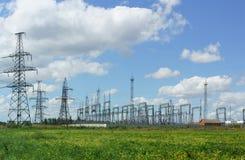 Freileitungsmast und elektrische Nebenstelle auf dem Gebiet und auf dem Hintergrund des blauen Himmels Lizenzfreie Stockfotografie