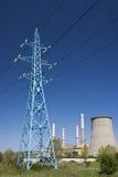 Freileitungsmast und Kraftwerk an einem hellen Tag Lizenzfreies Stockfoto