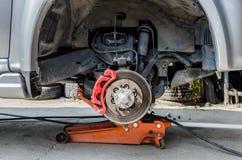 Frein à disque avant sur la voiture en cours du nouveau remplacement de pneu Image libre de droits