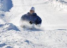 freinage en bas de l'homme de côte sledding Photo stock